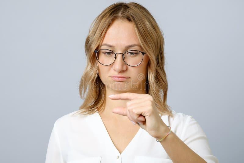 La jeune femme mécontente démontre quelque chose petite photo stock