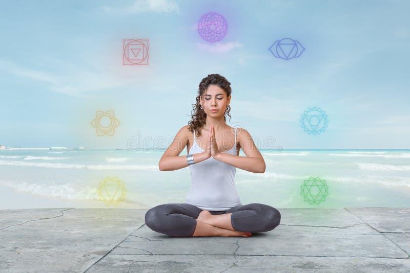 La jeune femme médite sur la plage avec des chakras rougeoyant autour de elle photos libres de droits