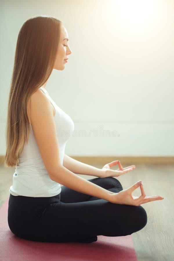 La jeune femme médite tout en pratiquant le yoga photo stock