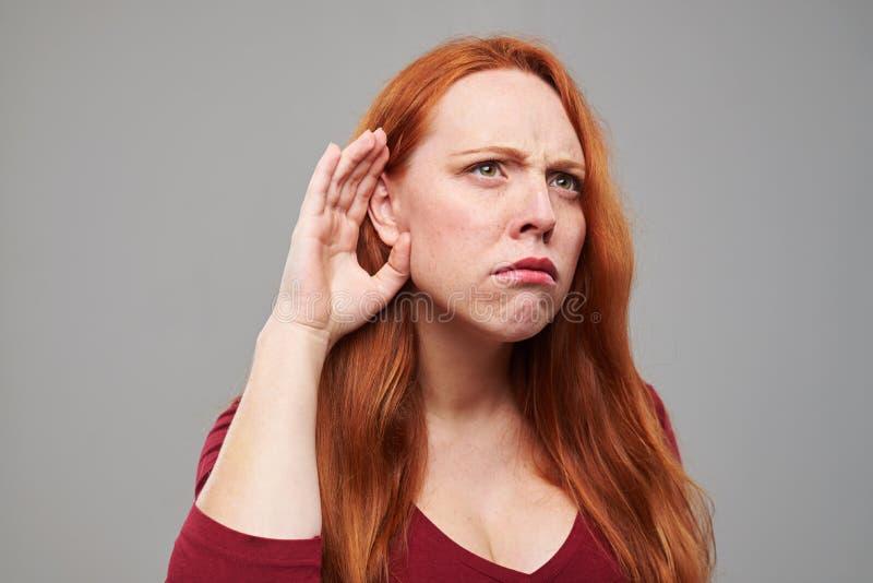 La jeune femme méfiante avec les cheveux rouges tient son nea de main photo stock