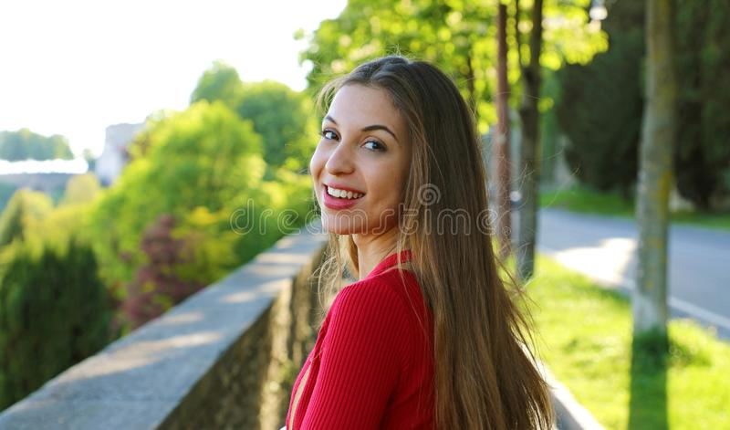 La jeune femme magnifique avec de longs cheveux tournent la tête et regarder la caméra en marchant dans la rue photo libre de droits