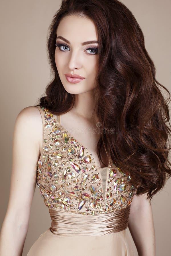 La jeune femme magnifique avec le maquillage de cheveux foncés et de soirée, porte la robe luxueuse images stock