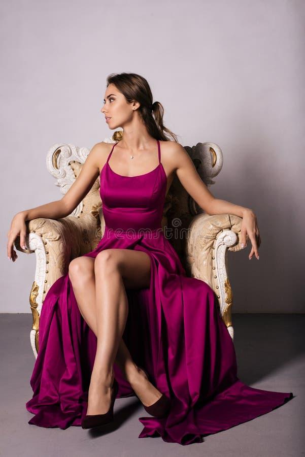 La jeune femme magnifique dans la robe luxueuse a s'assied dans des jambes croisées par chaise dans un appartement de luxe photos libres de droits