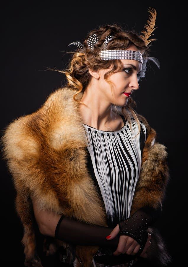 La jeune femme magnifique dans une peau de renard et plume dans la coiffure dans le style de Chicago image libre de droits