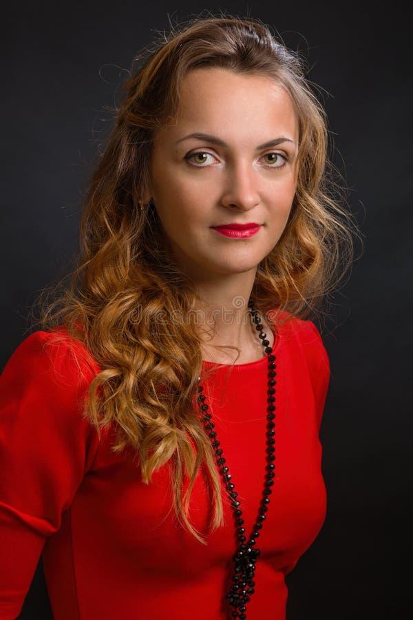 La jeune femme magnifique dans une robe élégante de couleur d'écarlate avec de belles boucles et perles photo libre de droits