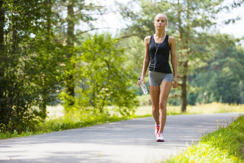 La jeune femme marche extérieur comme séance d'entraînement photos stock