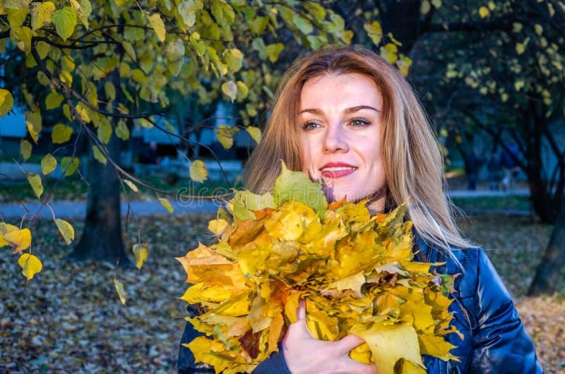 La jeune femme mignonne gaie de fille jouant avec le jaune tombé d'automne part dans le parc près de l'arbre, riant et souriant photographie stock