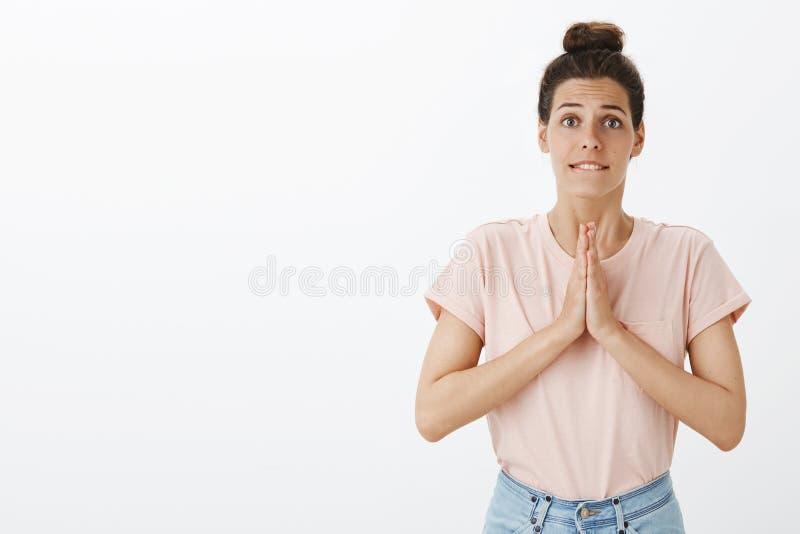 La jeune femme mignonne priante sincère avec le petit pain malpropre tenant des mains prient dedans au-dessus de la lèvre inférie image stock