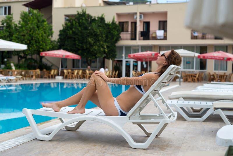 La jeune femme mince dans un bikini la prend un bain de soleil près de la piscine Une femme se trouve sur une chaise de plate-for photos libres de droits