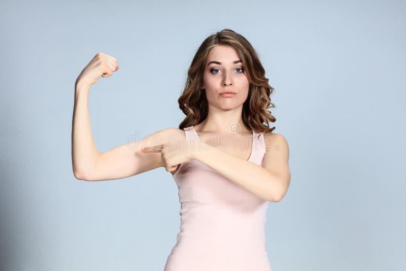 La jeune femme montrant ses muscles sur le fond gris photographie stock libre de droits