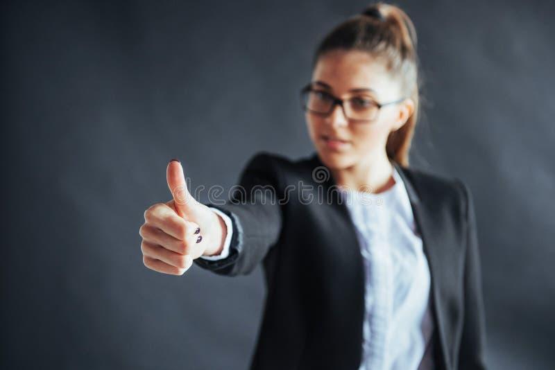 La jeune femme montre le pouce se tenant sur le fond noir, foyer en main photos stock
