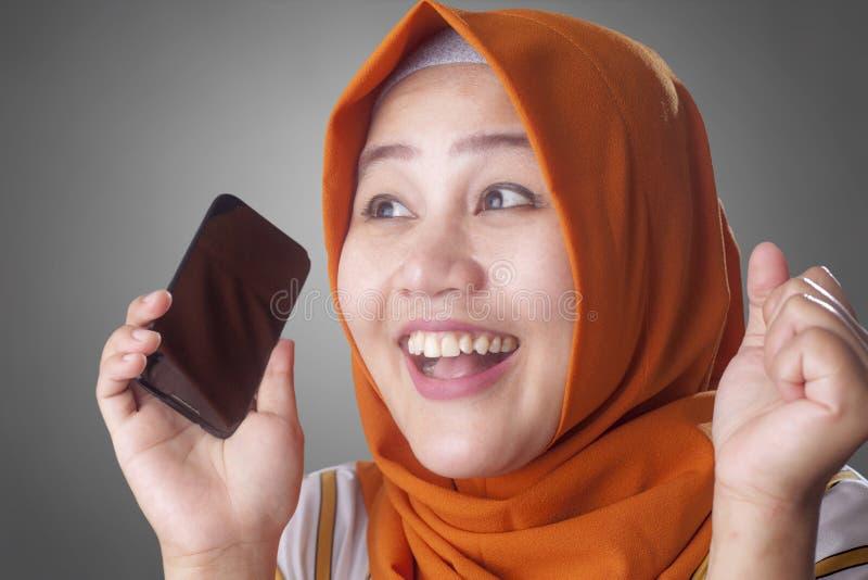 La jeune femme musulmane obtiennent de bonnes nouvelles ? son t?l?phone photographie stock