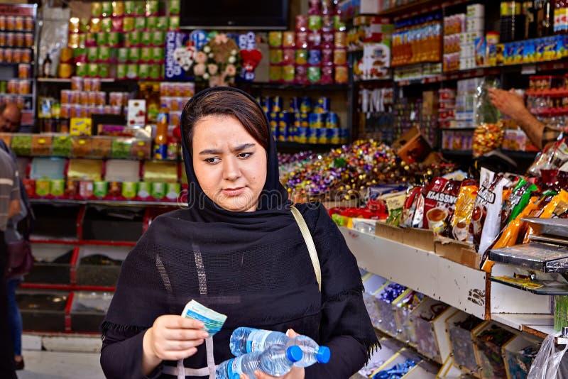 La jeune femme musulmane se tient dans l'épicerie, Téhéran, Iran images libres de droits