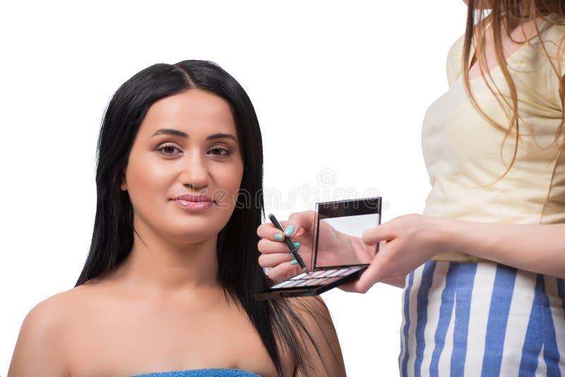 La jeune femme obtenant le maquillage d'isolement sur le blanc images stock