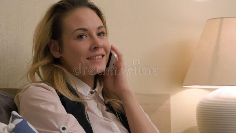 La jeune femme ont une conversation positive utilisant le téléphone portable se reposant sur le lit image libre de droits