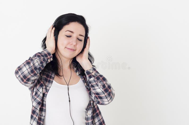 La jeune femme ou la fille écoutant sa chanson préférée a fermé des yeux et tenir de grands écouteurs avec des mains photos libres de droits