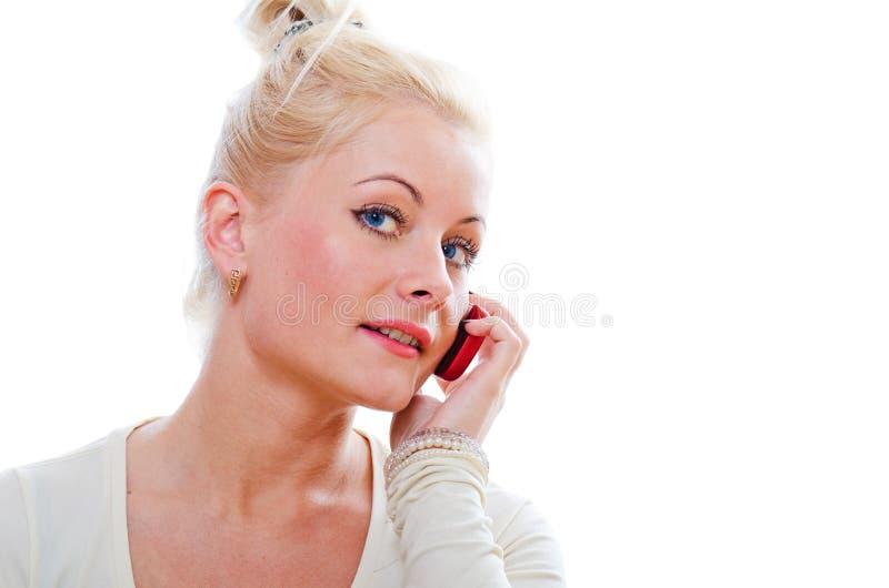 La jeune femme parle par un téléphone portable photographie stock