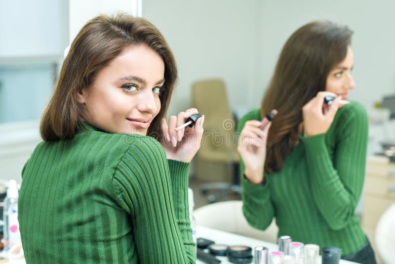 La jeune femme peint des lèvres dans le beige photo stock