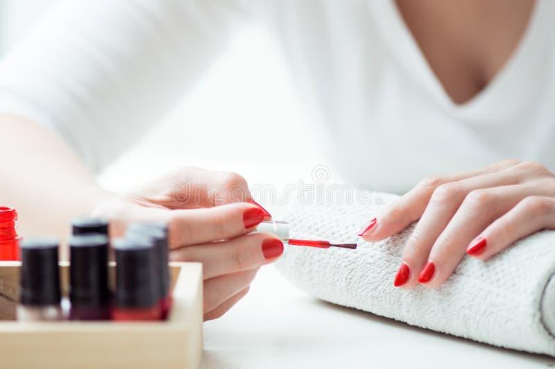 La jeune femme peint ses clous photographie stock