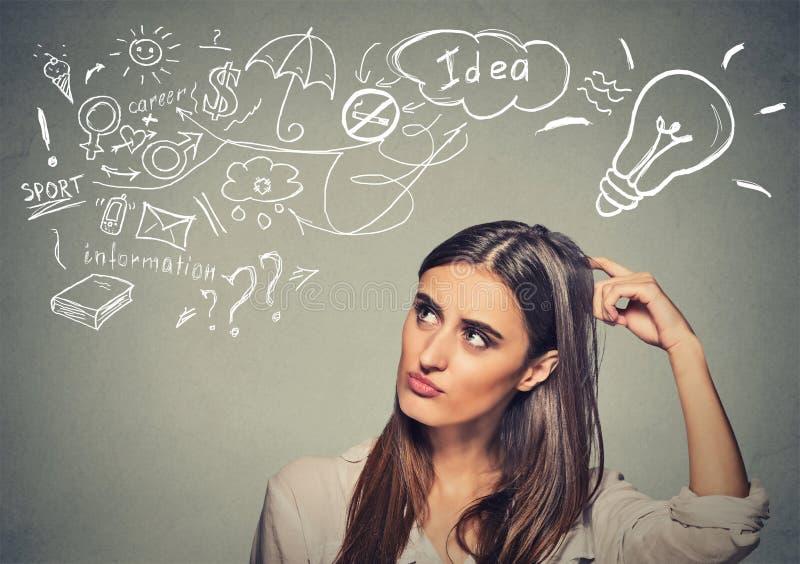 La jeune femme perplexe pensant rayant la tête a beaucoup d'idées recherchant images libres de droits