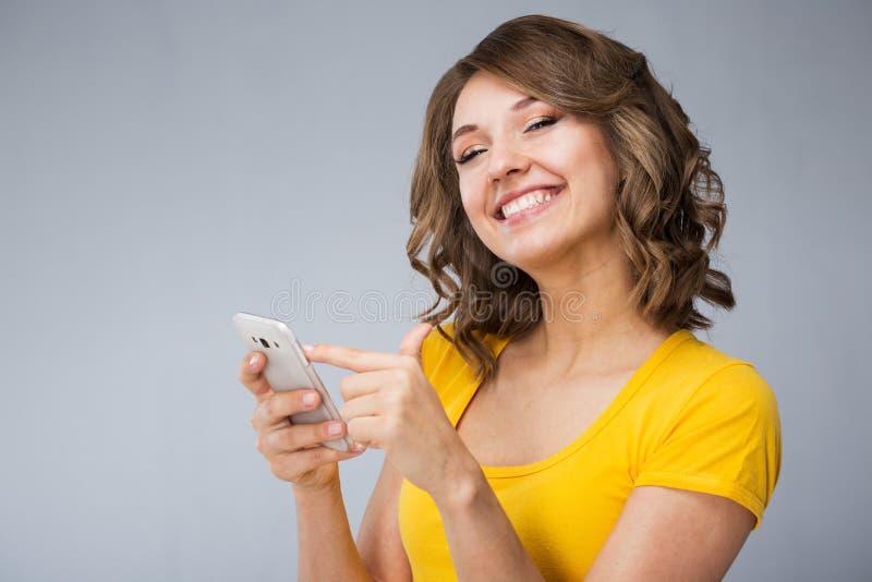 La jeune femme portant les caleçons jaunes de chemise et de jeans parlent au téléphone images stock