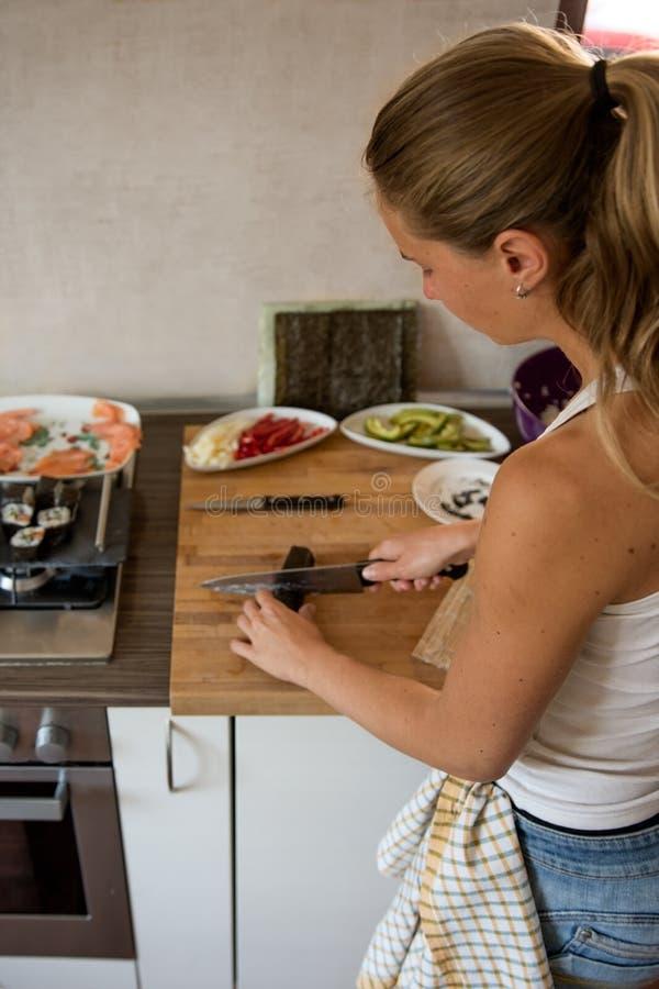 La jeune femme prépare le dîner asiatique dans la cuisine image libre de droits