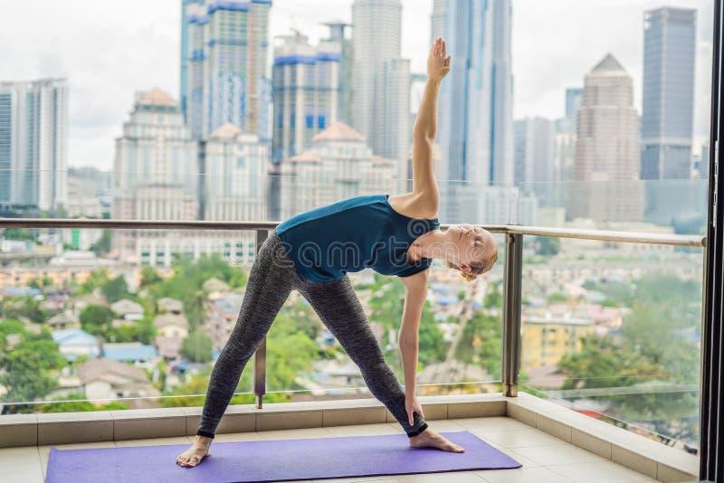 La jeune femme pratique le yoga pendant le matin sur son esprit de balcon images libres de droits