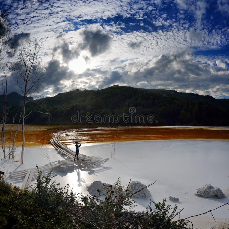 La jeune femme prenant des photos du rouge a pollué le lac en Roumanie, alba, images stock