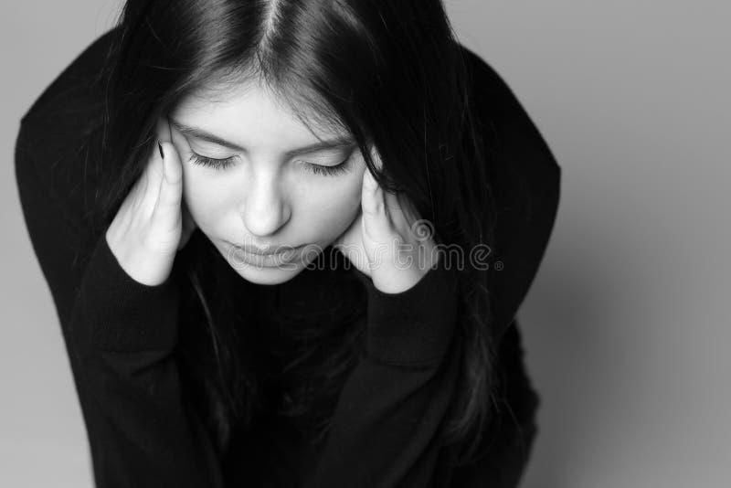 La jeune femme réfléchie avec remet sa tête photographie stock