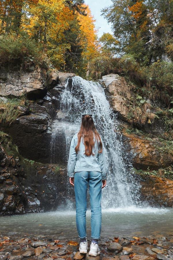 La jeune femme recule devant une cascade et recherche Paysage de forêt d'automne avec les arbres oranges et jaunes image stock