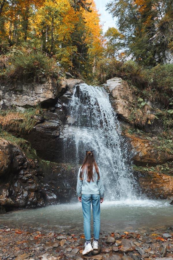 La jeune femme recule devant une cascade et recherche Paysage de forêt d'automne avec les arbres oranges et jaunes photos libres de droits