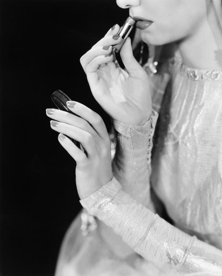 La jeune femme regardant dans un miroir et mettant dessus composent (toutes les personnes représentées ne sont pas plus long viva photo libre de droits