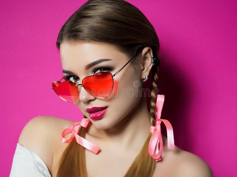 La jeune femme regarde au-dessus des verres en forme de coeur photographie stock libre de droits