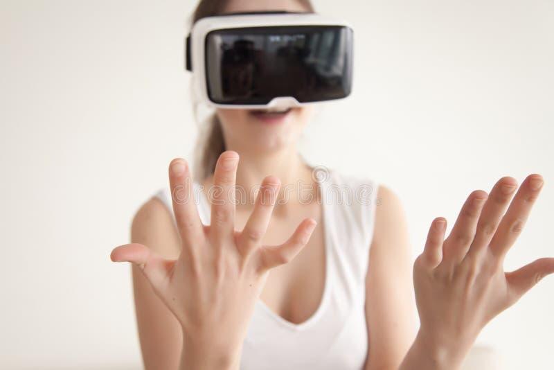 La jeune femme regarde sur propres mains par des verres de VR photos libres de droits