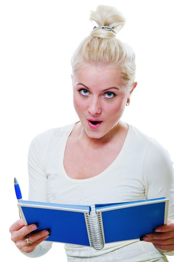 La jeune femme regarde une note dans un carnet photo libre de droits