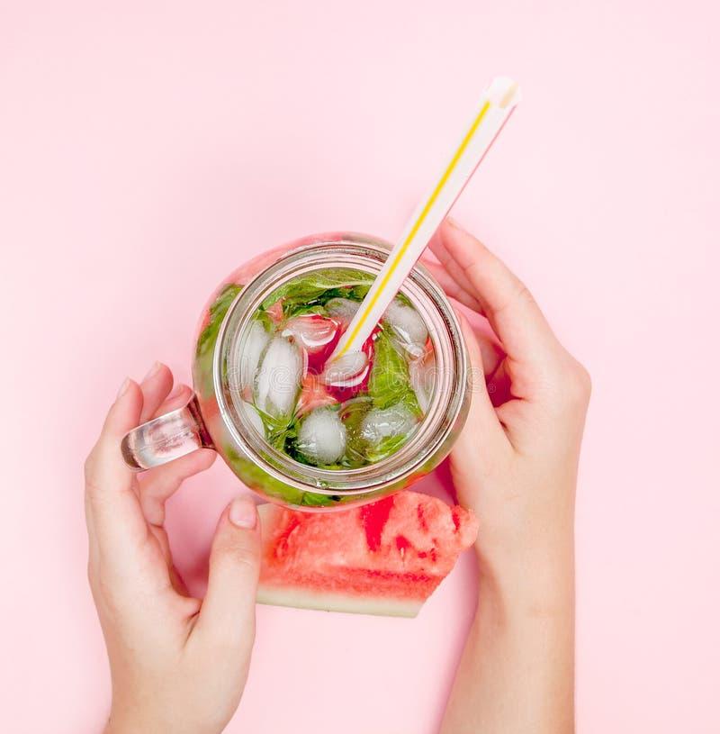 La jeune femme remet tenir la limonade fraîchement serrée de pastèque des agrumes Femelle avec le pot de maçon complètement du co photo stock