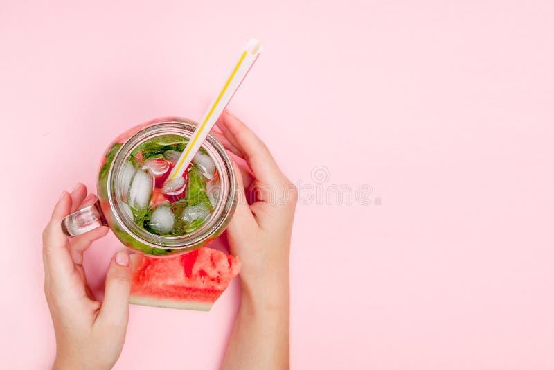 La jeune femme remet tenir la limonade fra?chement serr?e de past?que des agrumes Femelle avec le pot de ma?on compl?tement du co images libres de droits