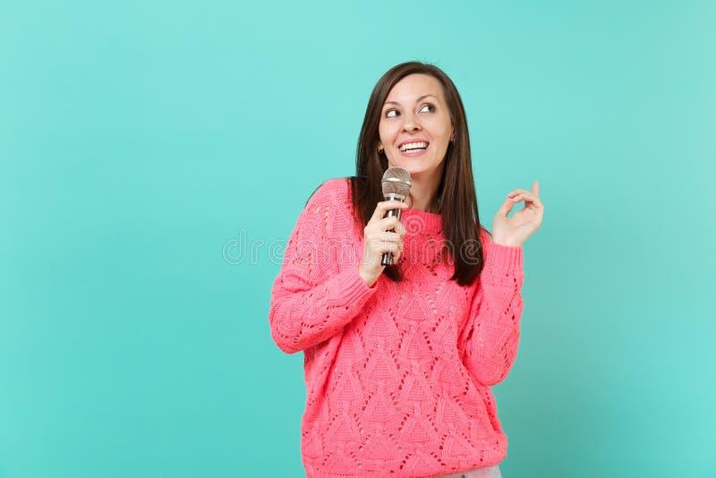 La jeune femme renversante dans le chandail rose tricoté recherchant la prise à disposition, chantent la chanson dans le micropho image stock
