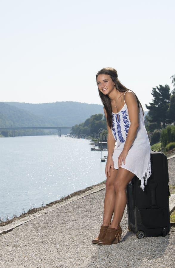La jeune femme renversante de brune pose dehors dans le bain de soleil blanc photos libres de droits