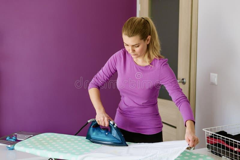 La jeune femme repasse la chemise blanche à bord photo stock