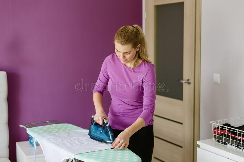 La jeune femme repasse la chemise blanche à bord image stock