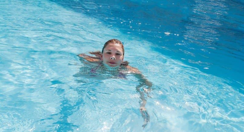 La jeune femme riante nage dans la piscine Repos de concept, résumé photos libres de droits