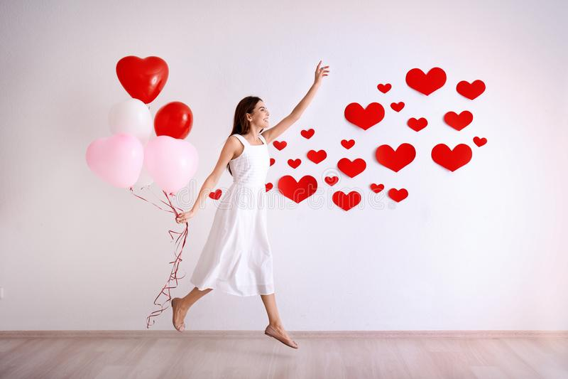 La jeune femme romantique avec des ballons s'approchent du mur photographie stock libre de droits