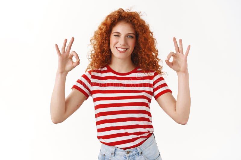 La jeune femme rousse bouclée chanceuse belle assurée clignant de l'oeil le geste avec plaisir de sourire satisfaisant d'ok d'ok  photographie stock libre de droits