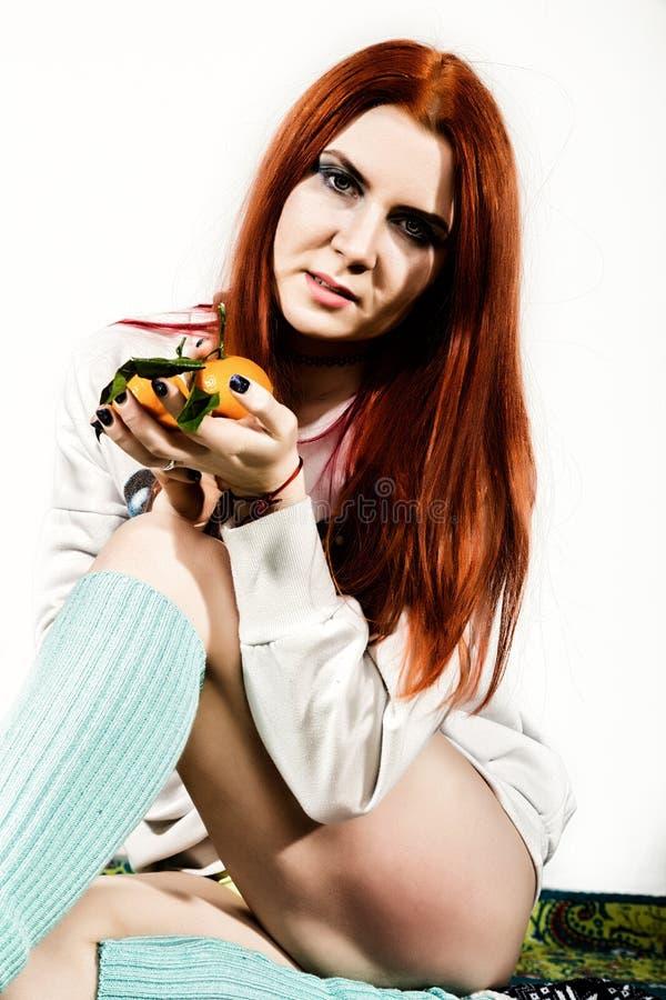 La jeune femme rousse mange du fruit orange d'agrume ayant l'amusement image stock