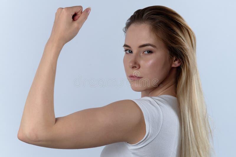 La jeune femme sûre attirante montre le biceps Portrait sur un whi images stock