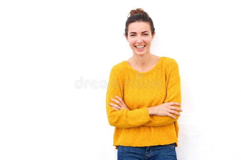 La jeune femme sûre riant avec ses bras a croisé sur le fond blanc photographie stock