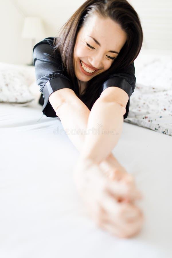 La jeune femme s'étendant dans le lit dans la robe de chambre noire a tendu ses mains vers la caméra photos stock