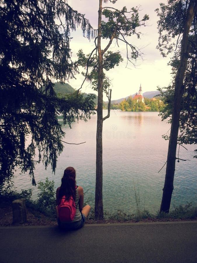 La jeune femme s'asseyant au rivage du lac a saigné image stock