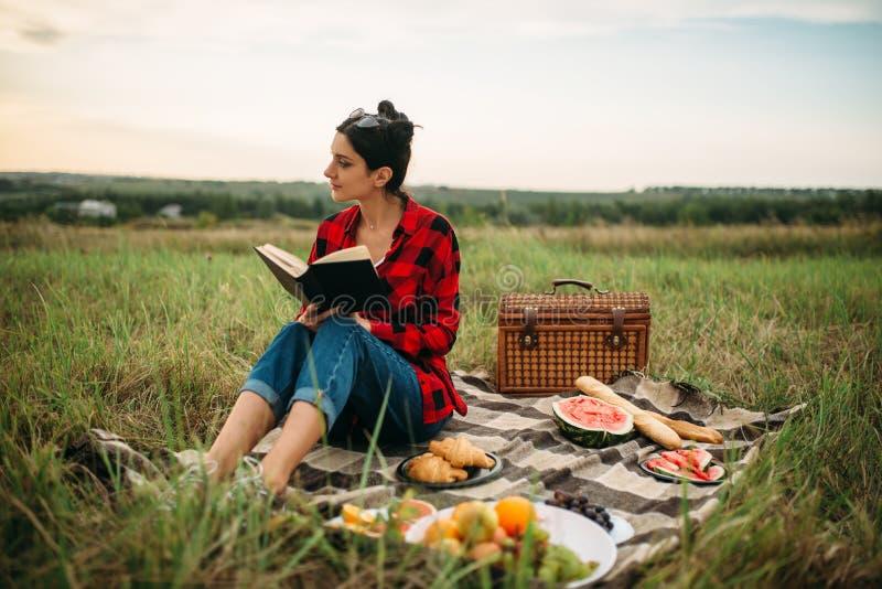 La jeune femme s'asseyant sur le plaid et lit le livre photo stock